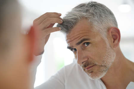40-year-old man checking hair in front of mirror Stok Fotoğraf