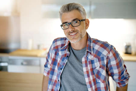 Smiling 40-year-old man standing at home Stock Photo