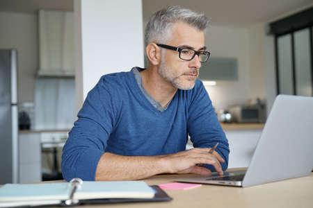 Mężczyzna w średnim wieku pracujący z biura domowego na laptopie Zdjęcie Seryjne