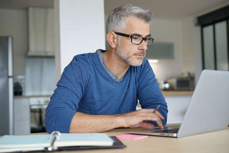 Middle-aged man working from home-office on laptop 免版税图像 - 89006895