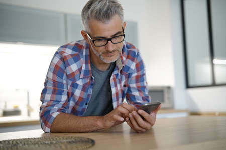 Middle-aged man at home using smartphone Banque d'images