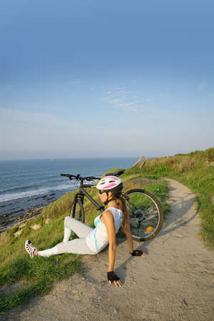 Athletic girl on bike ride, relaxing by the sea Banque d'images
