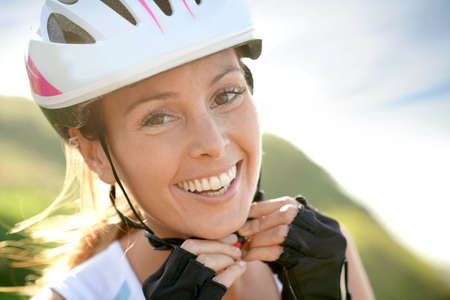 Portrait of smiling woman on bike ride putting helmet on