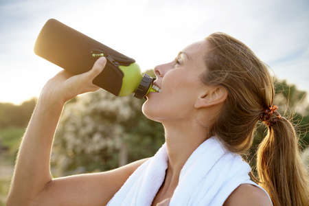 Portrait of fitness girl drinking water from bottle on jogging session