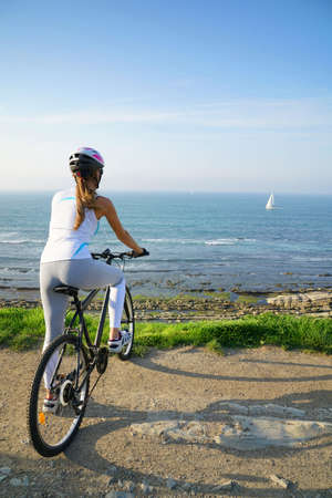 Woman riding bike by the sea