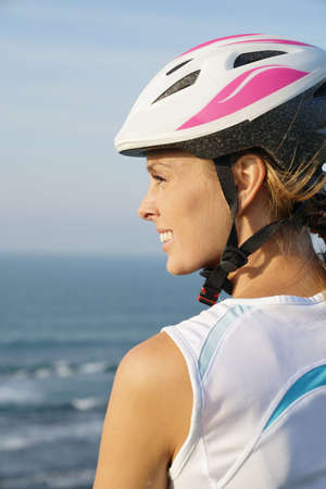 Profile view of woman on bike ride wearing protection helmet Banque d'images