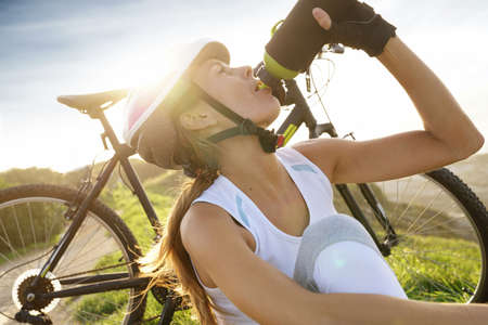 Portrait of woman on biking journey drinking water from bottle
