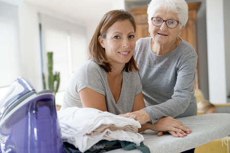 Portrait of elderly woman with housekeeper