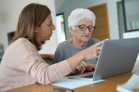 Elderly woman using laptop with help of homecarer 写真素材