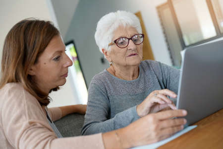 Elderly woman using laptop with help of homecarer Stock Photo