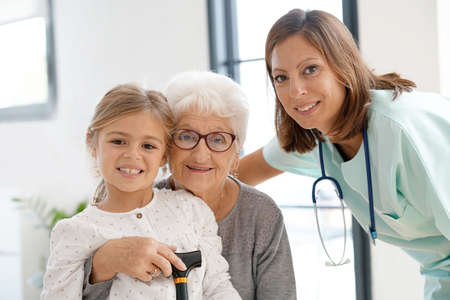 Old woman and grandkid at home with nurse