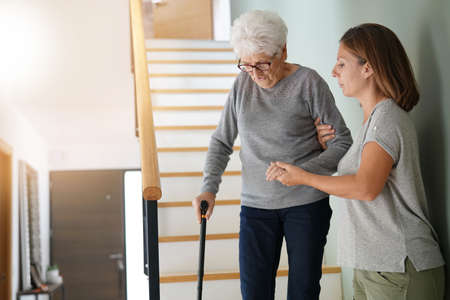 Homecare helping elderly woman going down the stairs