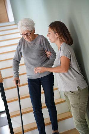 Thuiszorg die oudere vrouw helpt die de trap afloopt