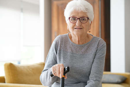Portrait of elderly woman sitting in sofa, holding cane Stock Photo