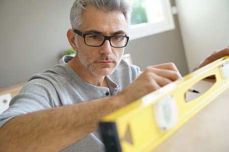 Man measuring wood piece for furniture assembling