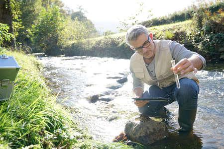 Biologe prüft Wasser der Fluss