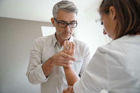 Fysiotherapeut die geduldige arm uitrekt