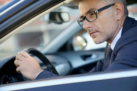 Portrait of businessman driving car for work 스톡 콘텐츠