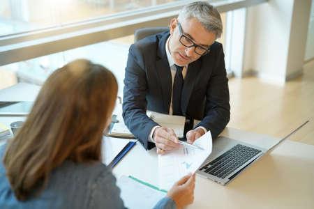 Vrouw die in het bureau van bankier financiële lening voor project ondertekent