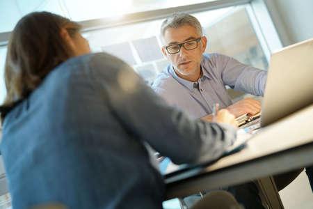 Collègues travaillant ensemble dans le bureau, en utilisant un ordinateur portable