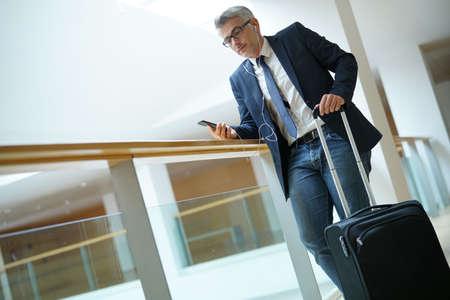 Homme d'affaires avec valise au hall de départ de l'aéroport