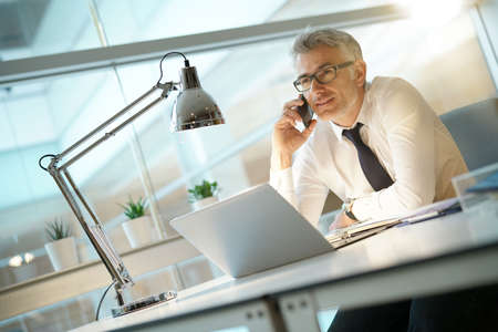 Businessman in office talking on smartphone Stock Photo