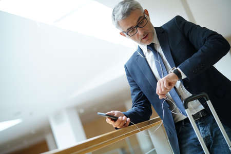 Businessman at airport checking time on watch for flight departure