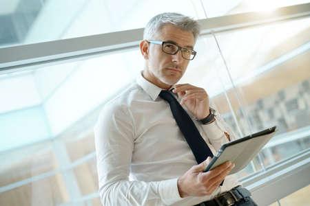 Homem negócios, em, escritório, conectado, com, tablete digital Foto de archivo - 90549591