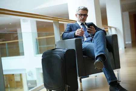Businessman in airport waiting area connected with smartphone Archivio Fotografico