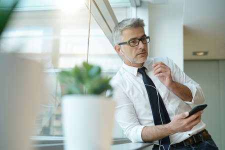 Businessman talking on phone in office, standing by window