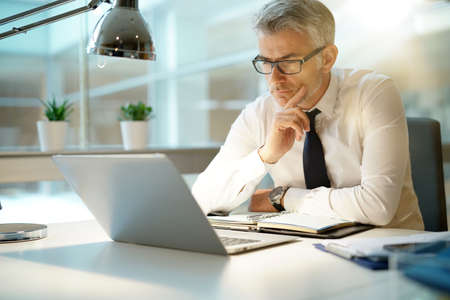 Businessman working on laptop in office, being concerned Stockfoto