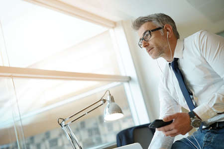 Businessman talking on phone in office, sitting on desk