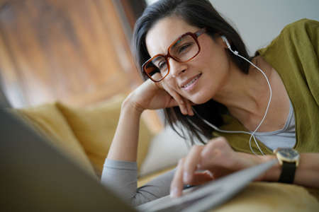 Trendy woman relaxing at home connected with laptop Stock Photo