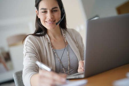 Home-office teleoperator talking on phone with headset