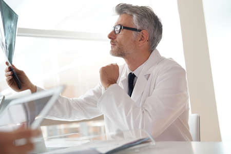 Mature doctor in office looking at Xray results