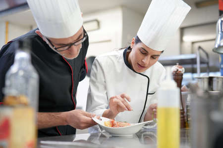 Professional cook chefs in kitchen improving dish composition
