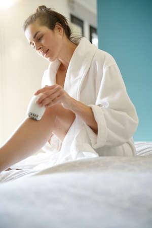 Woman in bedoom shaving legs with electric razor