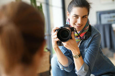 Photographer in private house taking picture of model Standard-Bild