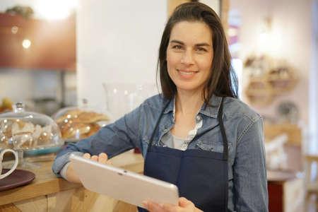 Empregada de mesa no café que toma a ordem na tabuleta digital Foto de archivo - 91613729