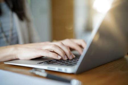 CLoseup of woman typing on laptop keyboard