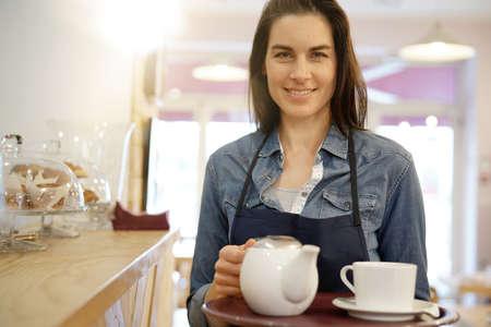 Waitress in coffee shop holding tray Standard-Bild