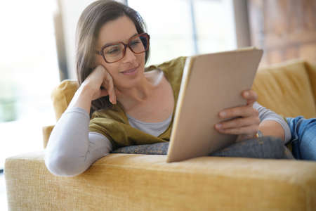 Brunette woman with eyeglasses using tablet, sitting on sofa