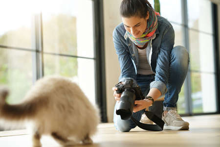 Woman photographer taking pictures of cat