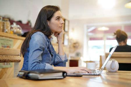 Woman working on laptop computer in coffee shop Standard-Bild
