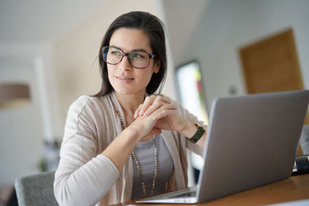 Home-office businesswoman looking by window