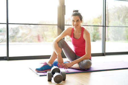 Cheerful woman sitting on floor in fitness outfit Standard-Bild