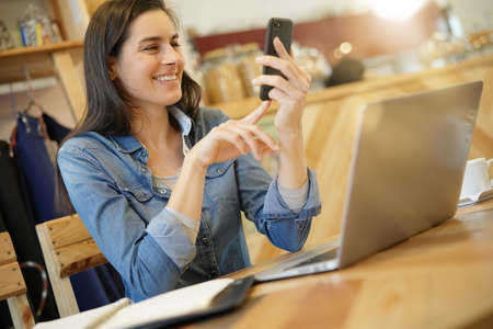 Woman talking on phone while working at coffee shop table