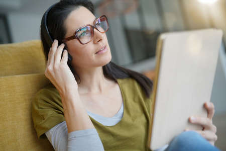 Woman at home connected with tablet and headset