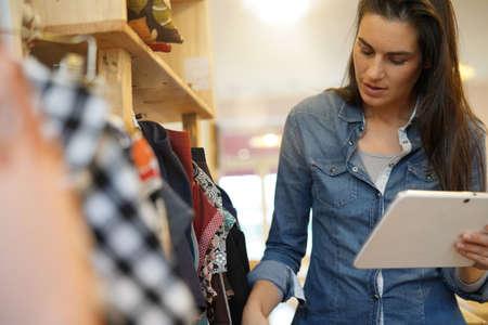 Shop owner checking stocks with digital tablet Standard-Bild