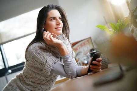Brunette girl with long hair talking on phone with earphones Standard-Bild